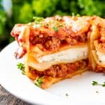 A Mini Lasagna Cup cut in half-layered with cheese, sausage, sauce and noodles, topped with chopped fresh parsley