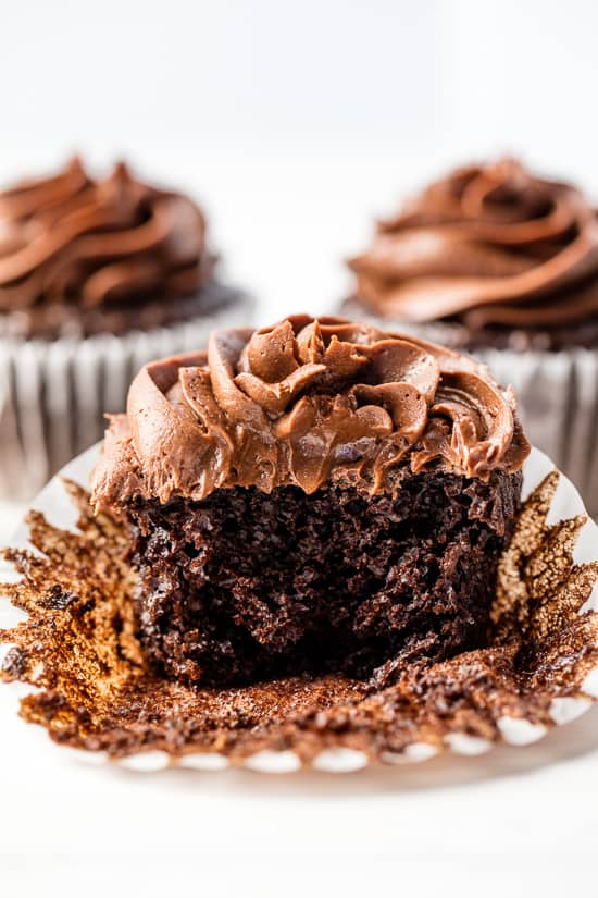 A moist chocolate cupcake with chocolate frosting with a bite taken out of it