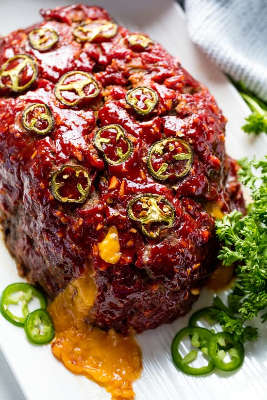 Jalapeno Cheddar Stuffed Meatloaf topped with Jalapenos sitting on a white platter.