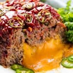 Jalapeno Cheddar Stuffed Meatloaf cut in half with the cheddar cheese oozing out.