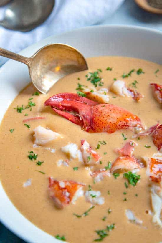Lobster Bisque in a white bowl with a brass spoon in it.
