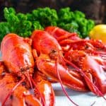 Three cooked lobsters on a serving plater with leafy greens and lemon in the background.