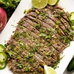 Slow Cooker Carne Asada sliced and served on a platter with cilantro, lime wedges and slices of jalapeno