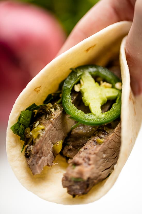 Slow Cooker Carne Asada Taco with slices of jalapeno and cilantro