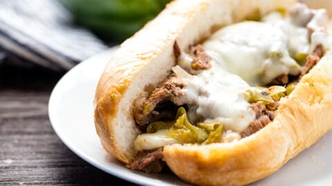 Angled view of Philly Cheese Steak with green bell peppers and melted Kraft provolone cheese on a hoagie roll.