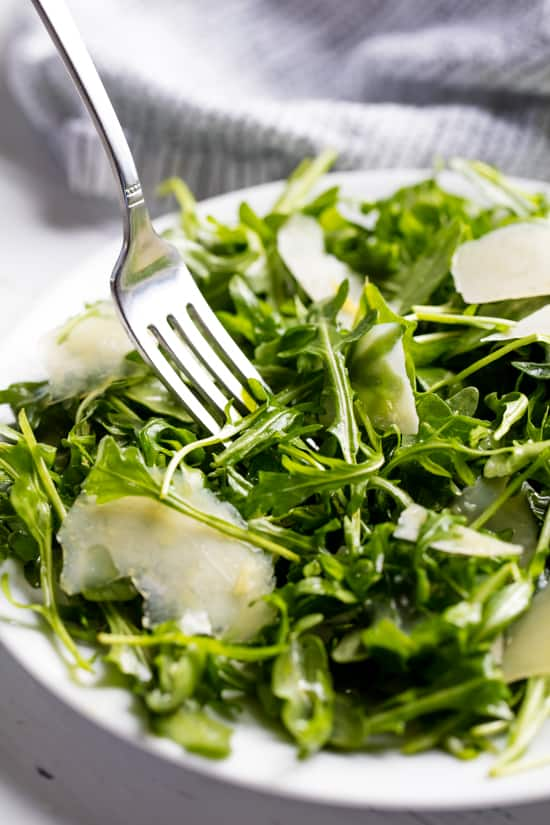 Arugula Salad served up on a white plate with a fork in it.