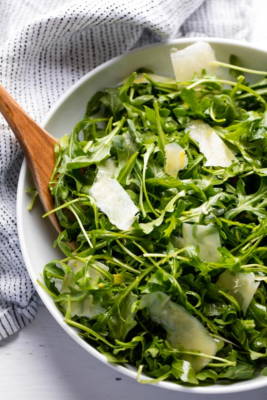 Arugula salad in a white bowl with a wooden spoon in it.