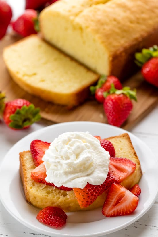 Slice of Pound Cake with sliced strawberries and whip cream on it.