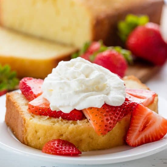 Slice of Pound Cake with sliced strawberries and whip cream on it sitting on a white plate.