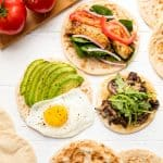 Bird's eye view of 3 flatbread recipes, an avocado and egg flatbread, a muhsroomm and arugula flatbread, and spinach, onion, grilled chicken, and tomato flatbread.