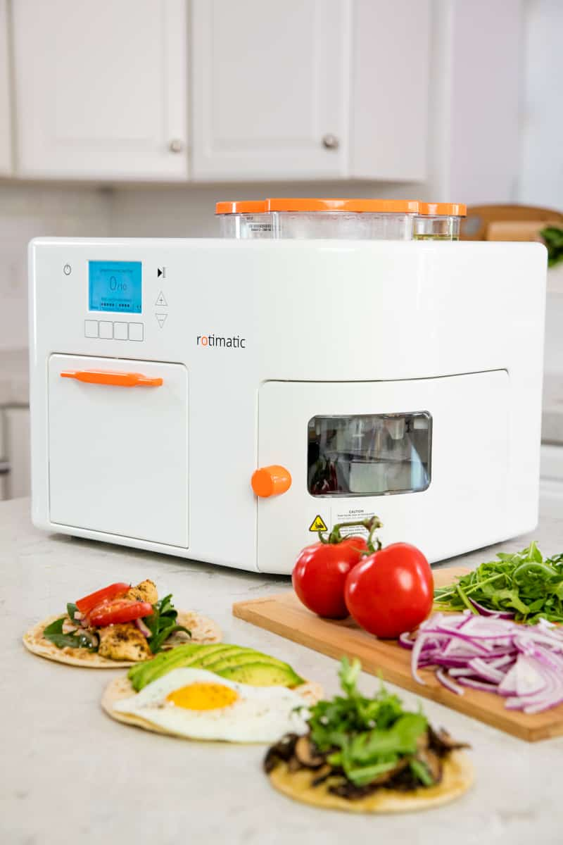 Rotimatic sitting on a countertop with some completed flatbread recipes and ingredients.