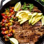 Mexican Skillet Steak in a skillet topped with avocado slices and two lime wedges all sitting next to a side of pico de gallo.