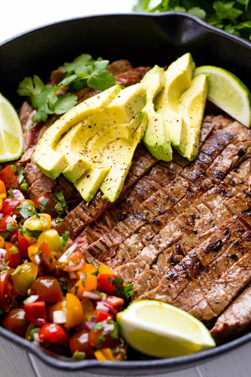 Close up of Mexican Skillet Steak in a skillet topped with avocado slices and two lime wedges all sitting next to a side of pico de gallo.