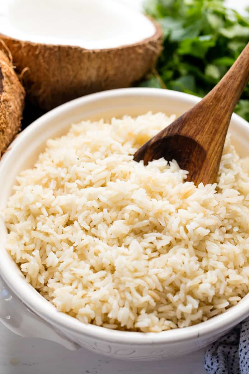 Coconut Rice in a white bowl with a wooden spoon in it.