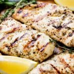 Grilled Chicken on a cutting board with lemon wedges.