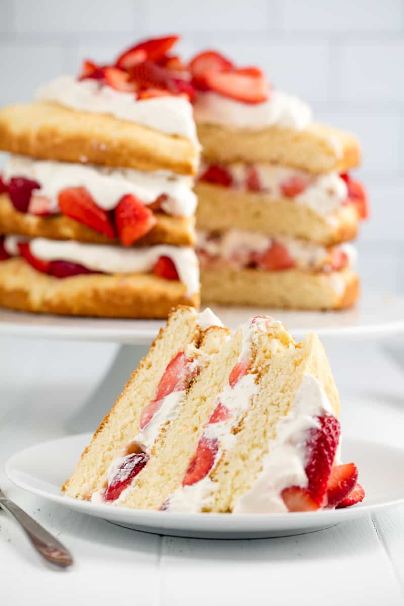 A slice of Strawberry Shortcake on a white plate with the rest of the cake behind it.