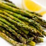 Grilled Asparagus on a white plate with a lemon wedge.