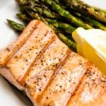 Grilled Salmon on a white plate with asparagus and a lemon wedge.