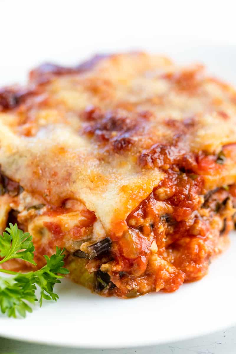 A slice of Eggplant Lasagna topped with bubbly cheese and garnished with a sprig of parsley
