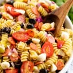 A white bowl full of Pasta Salad with a large wooden spoon in it.