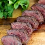 A sliced up hanger steak on a cutting board.
