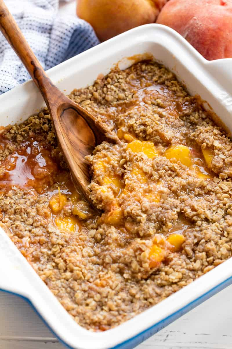 Peach Crisp in a 9 x 9 pan getting scooped up by a wooden spoon.