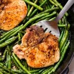 Bird's eye view of Pork Chops and Green Beans in a cast-iron skillet.