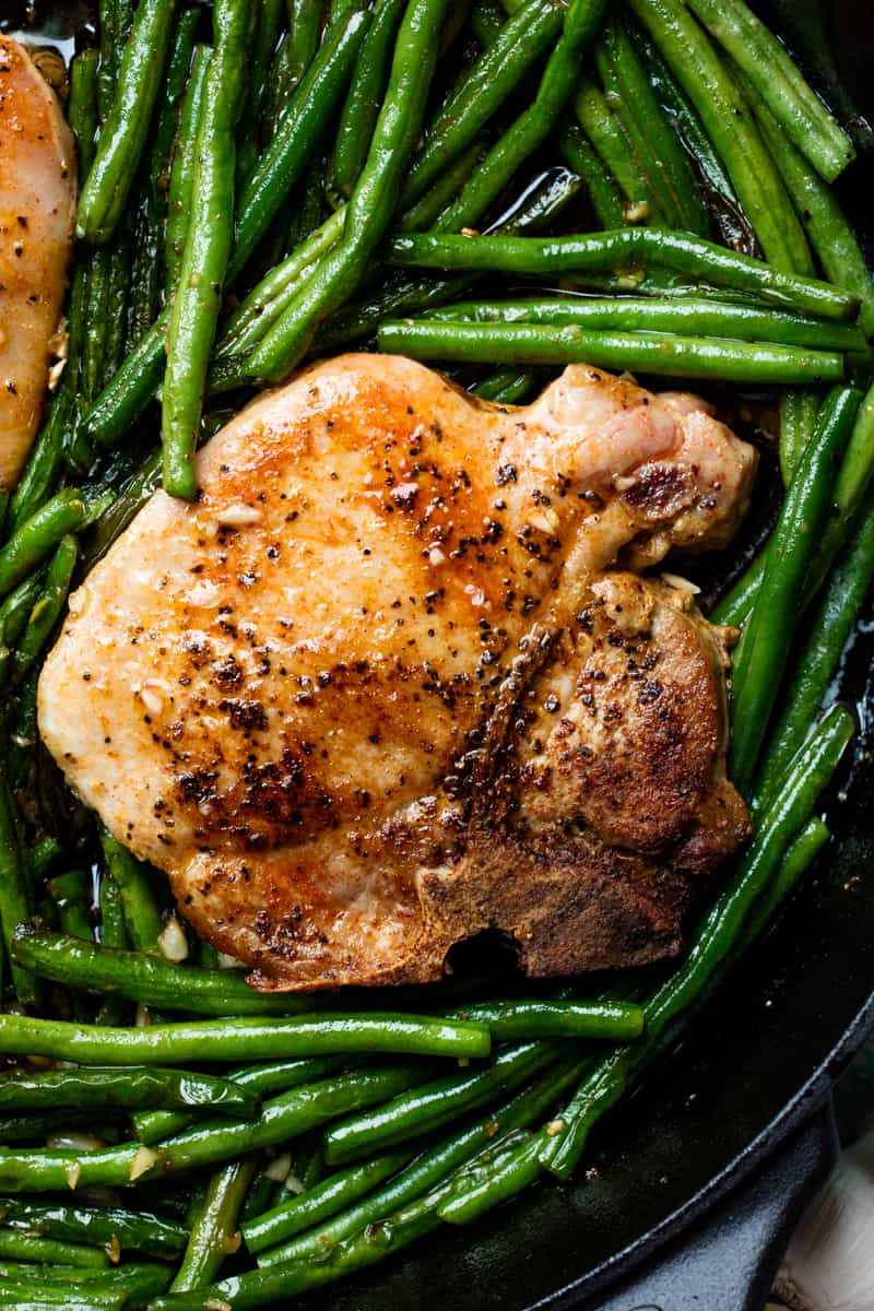 Close up of a pork chop surrounded by green beans in a cast-iron skillet.