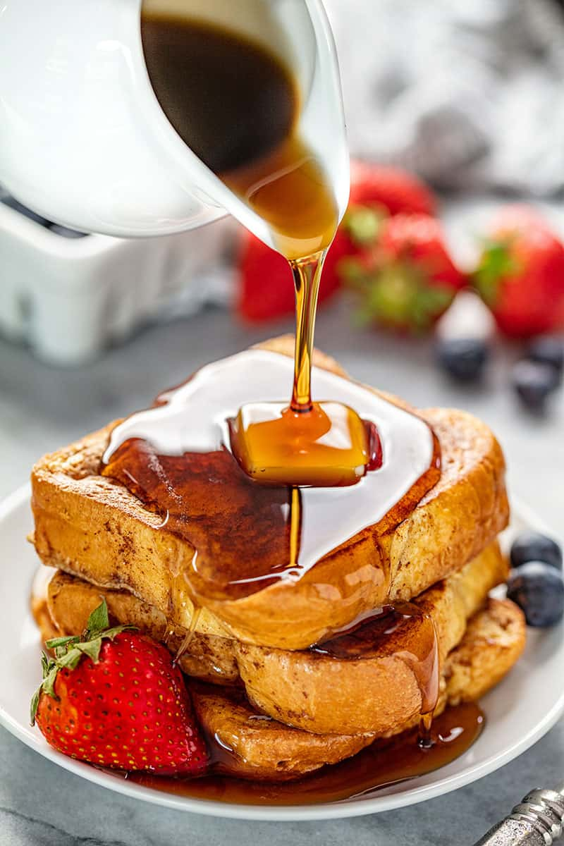 A stack of French Toast with a pad of butter on it getting syrup poured all over it.