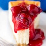 Close up of a slice of New York Cheesecake topped a cherry topping with a bite taken out of it on a white plate.
