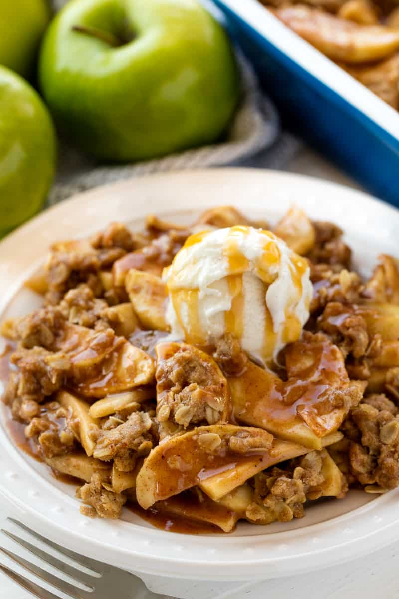 Apple Crisp served up on a white plate topped with a scoop of ice cream and caramel.