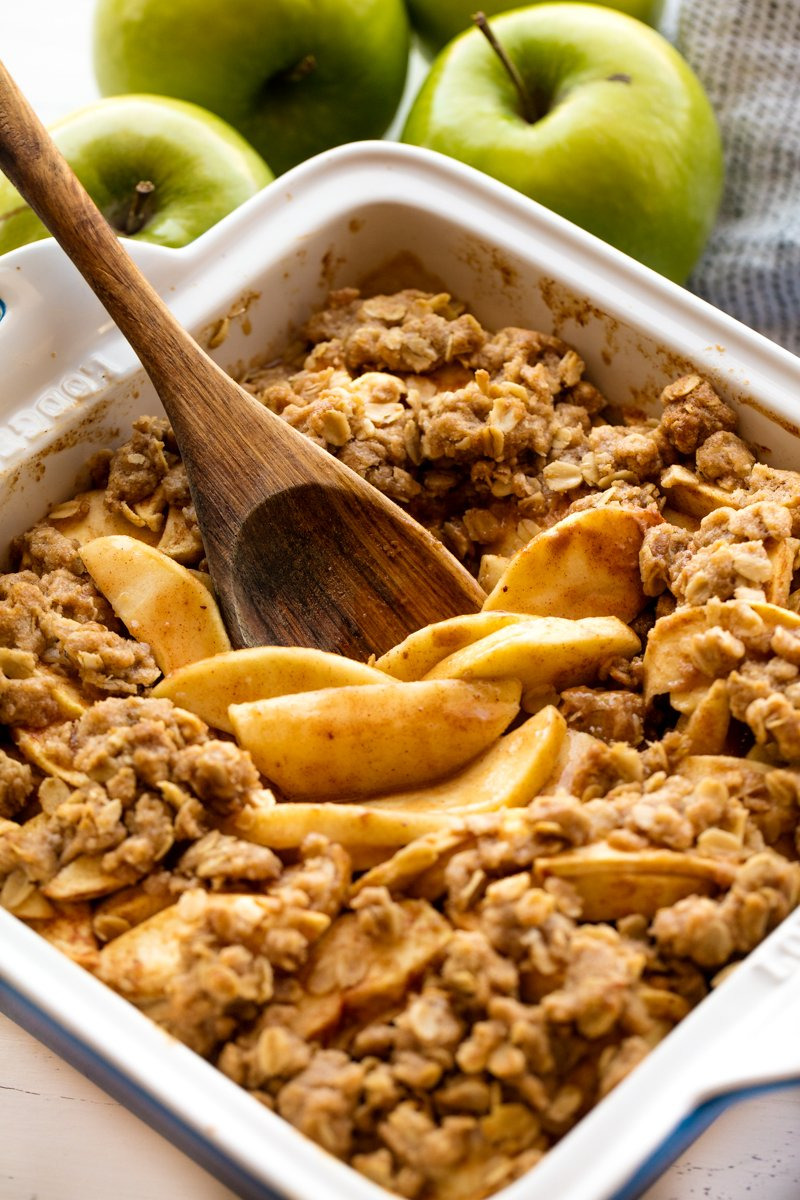 Apple Crisp in a baking dish with a wooden spoon in it.