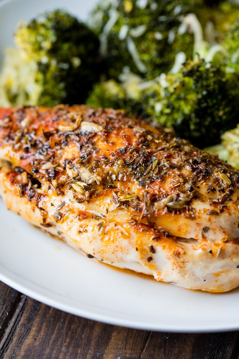 An herb stuffed chicken breast on a plate with broccoli.