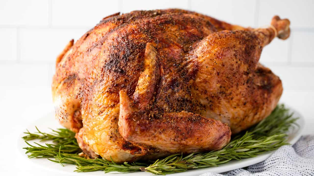 Juicy Roast Turkey on rosemary on a white serving dish.