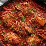 Bird's eye view of Chicken Cacciatore in a cast-iron skillet.