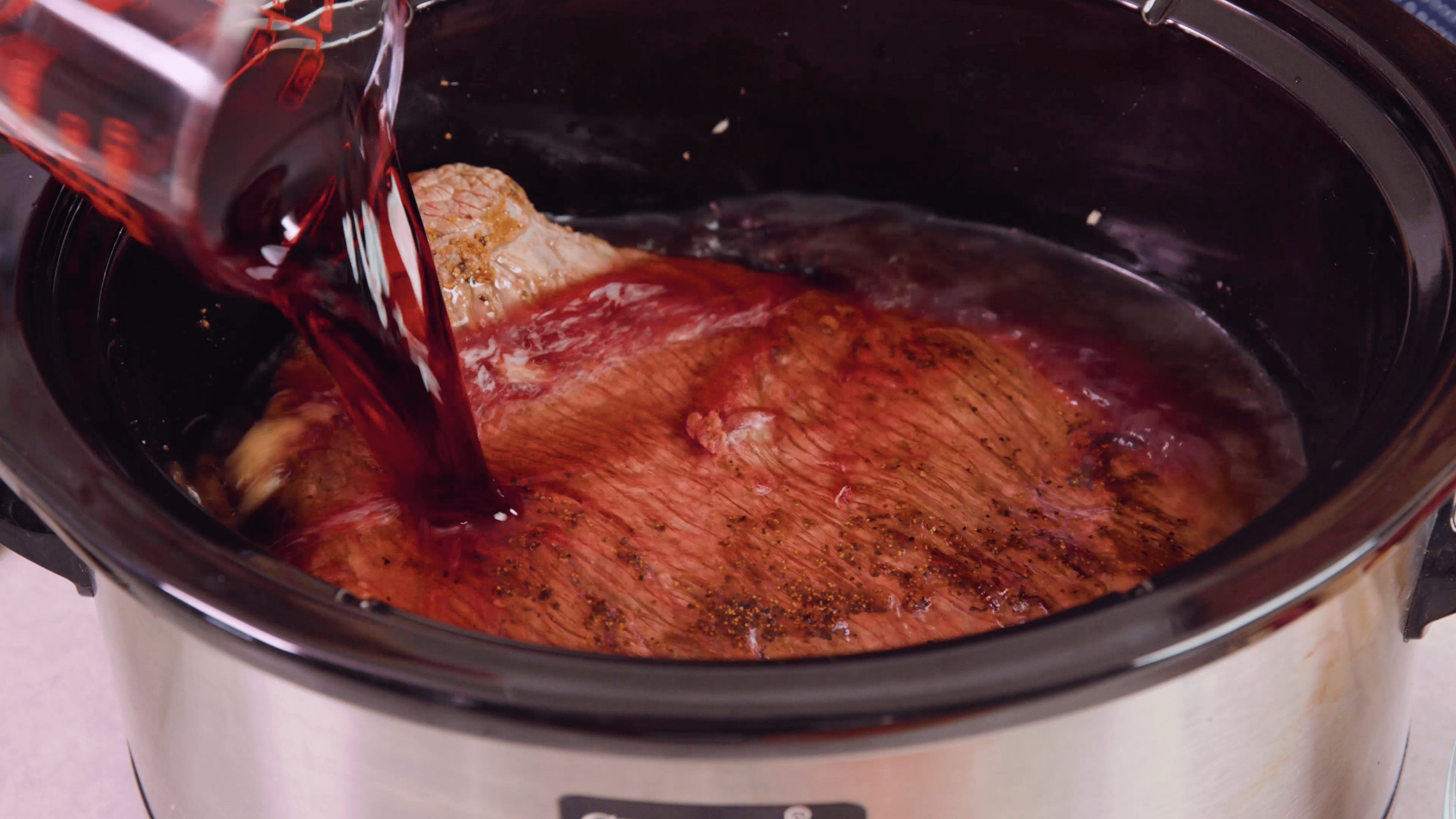 Red wine being poured onto the pot roast.
