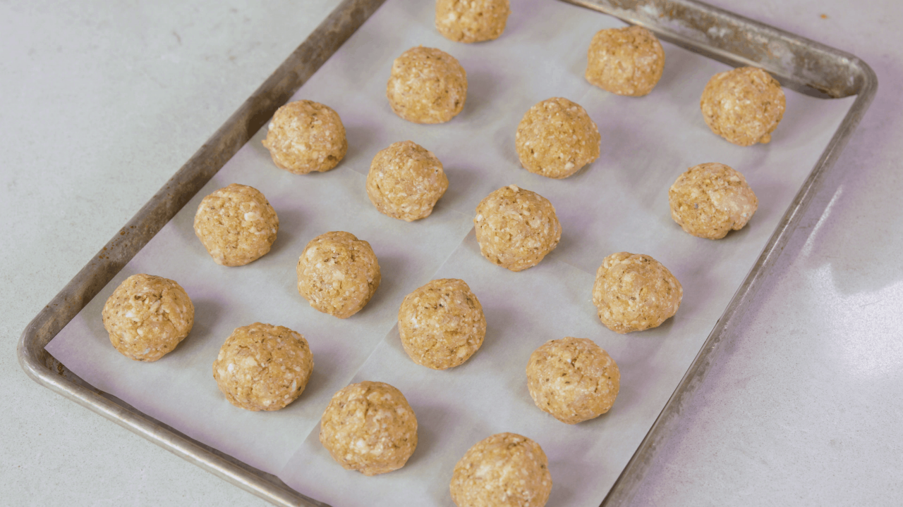 Raw chicken meatballs laying on a parchment paper-covered baking sheet.