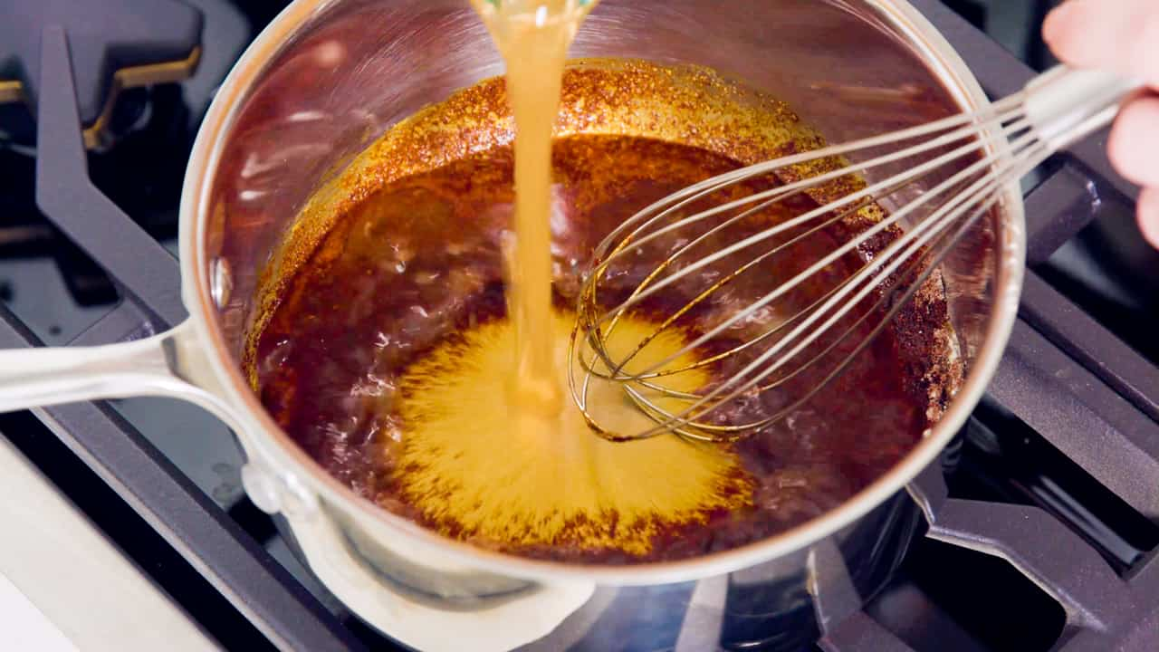 Vegetable broth being poured into a pot full of enchilada sauce ingredients.