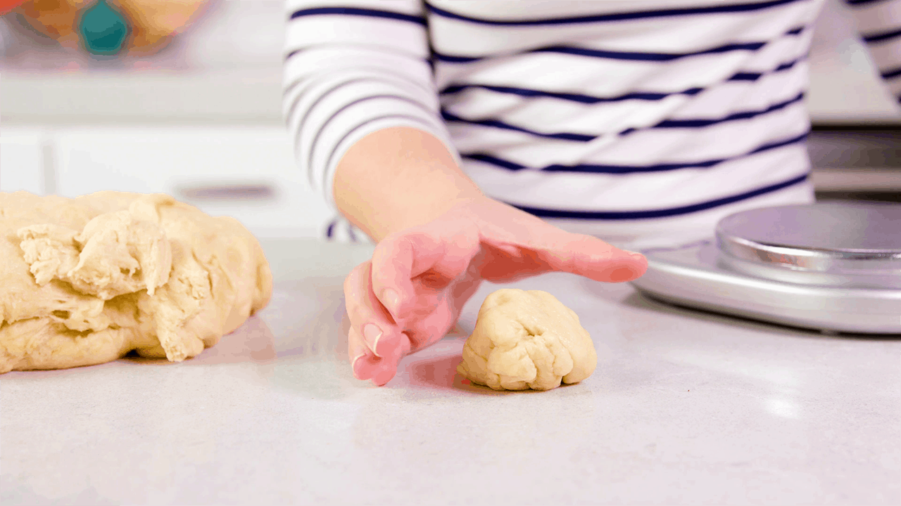 Shape your rolls by placing your hand into a cupping shape parallel to a clean countertop. Roll the dough in a circular motion between your palm and the countertop.