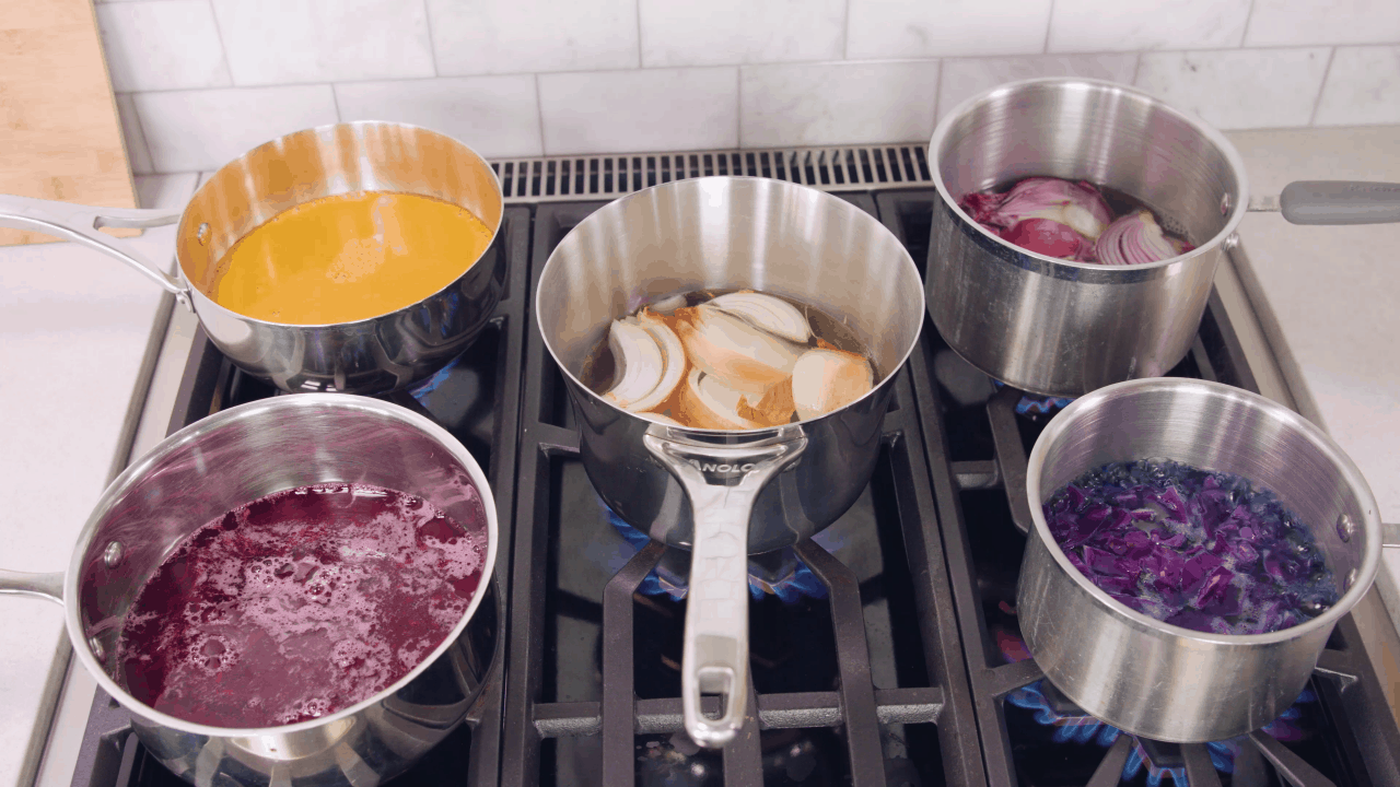 Five pots on the stove each with different ingredients in it.