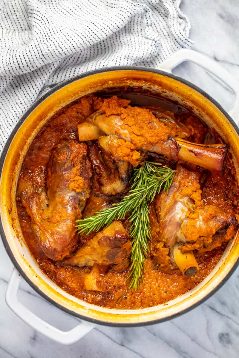 Bird's eye view of Braised Lamb Shanks in a ceramic cooking pot.