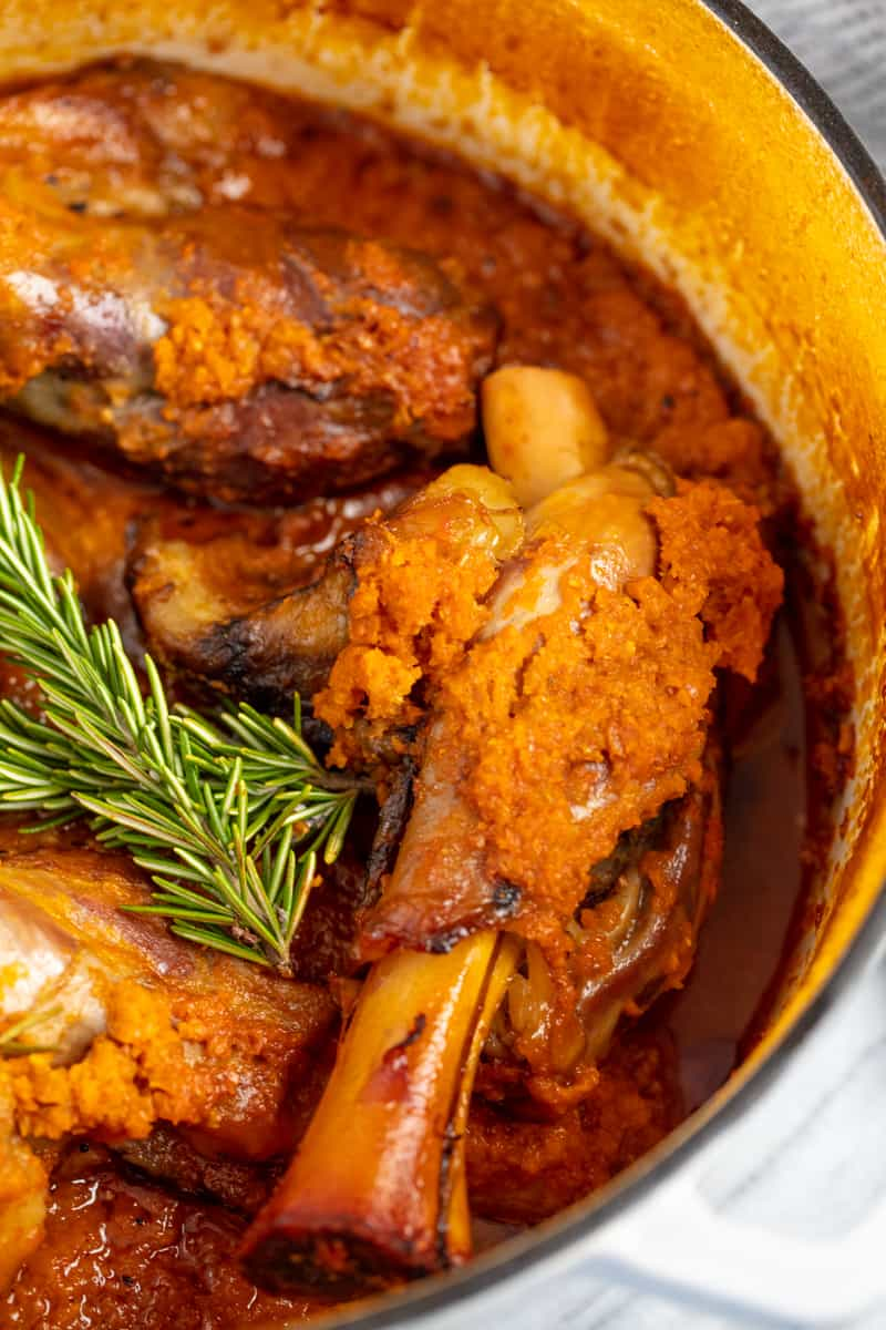 Close up of Braised Lamb Shank in a cooking pot.