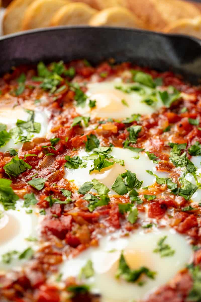 Close up Shakshuka in a cast iron skillet.