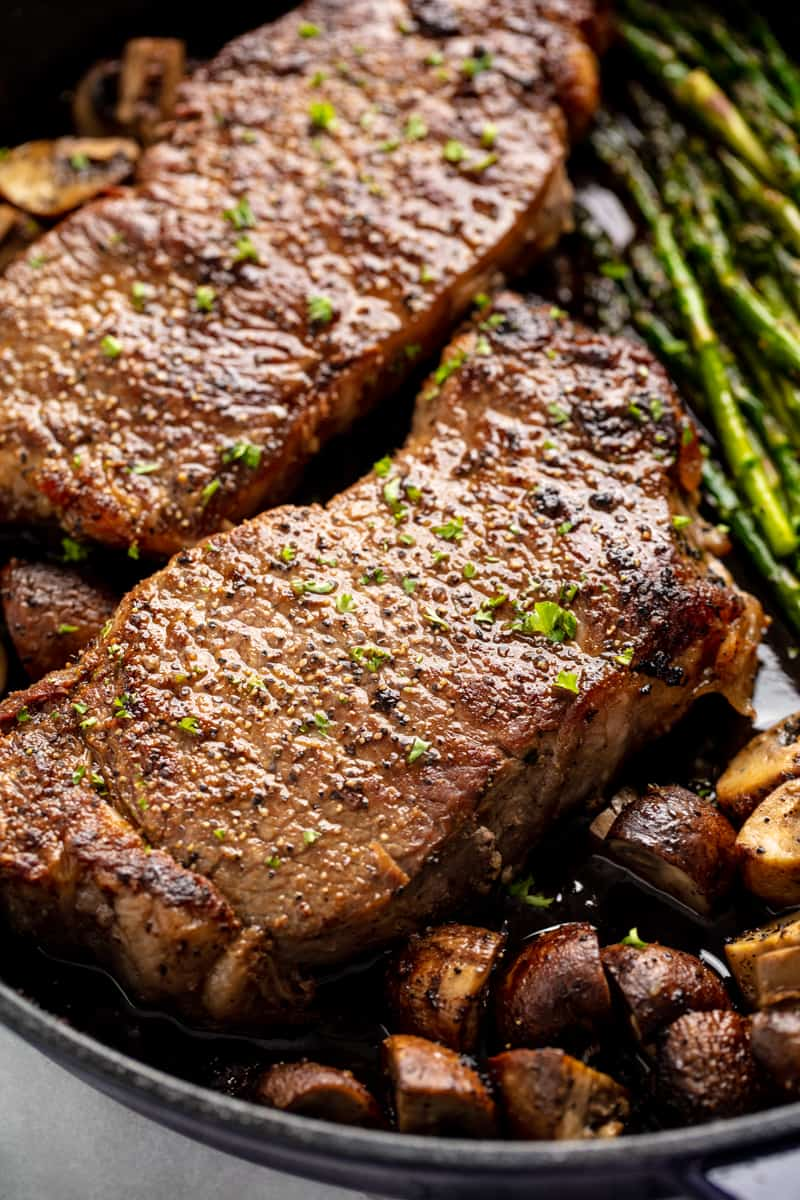 Close up of Skillet Steak with Asparagus and Mushrooms in a cast-iron skillet.
