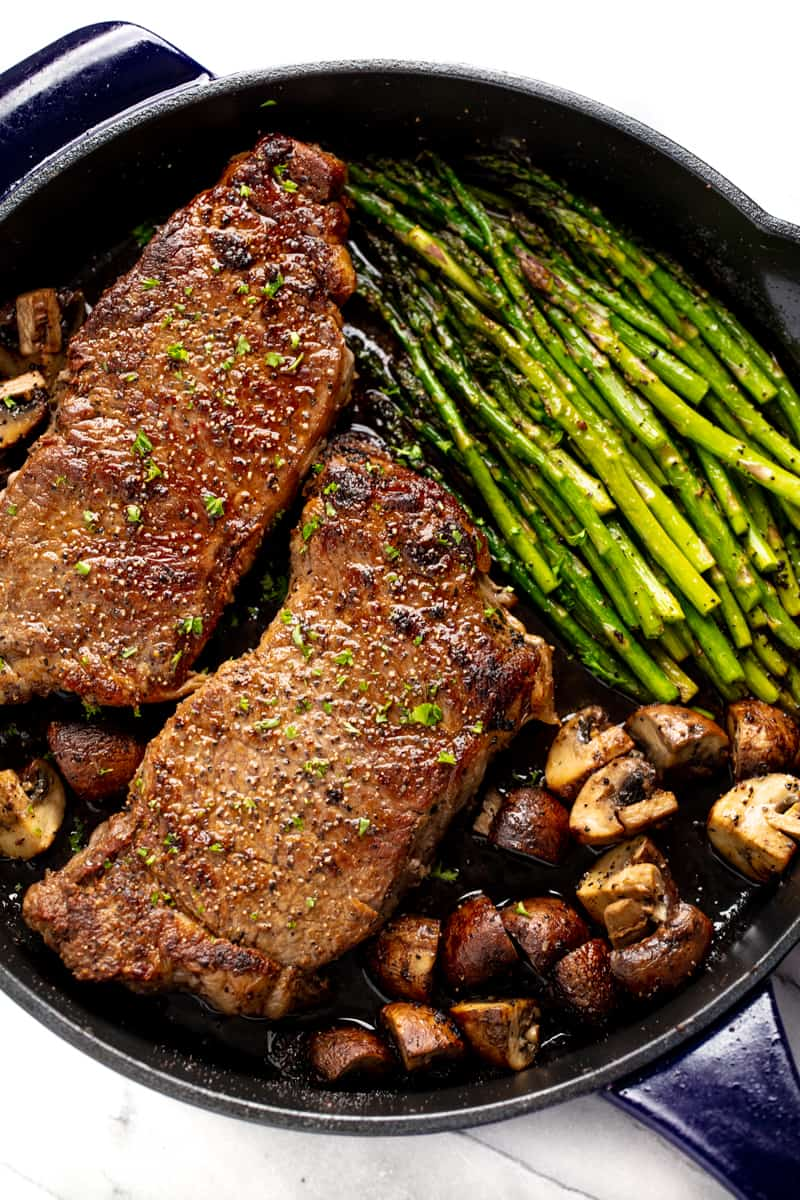Skillet Steak with Asparagus and Mushrooms in a cast-iron skillet.