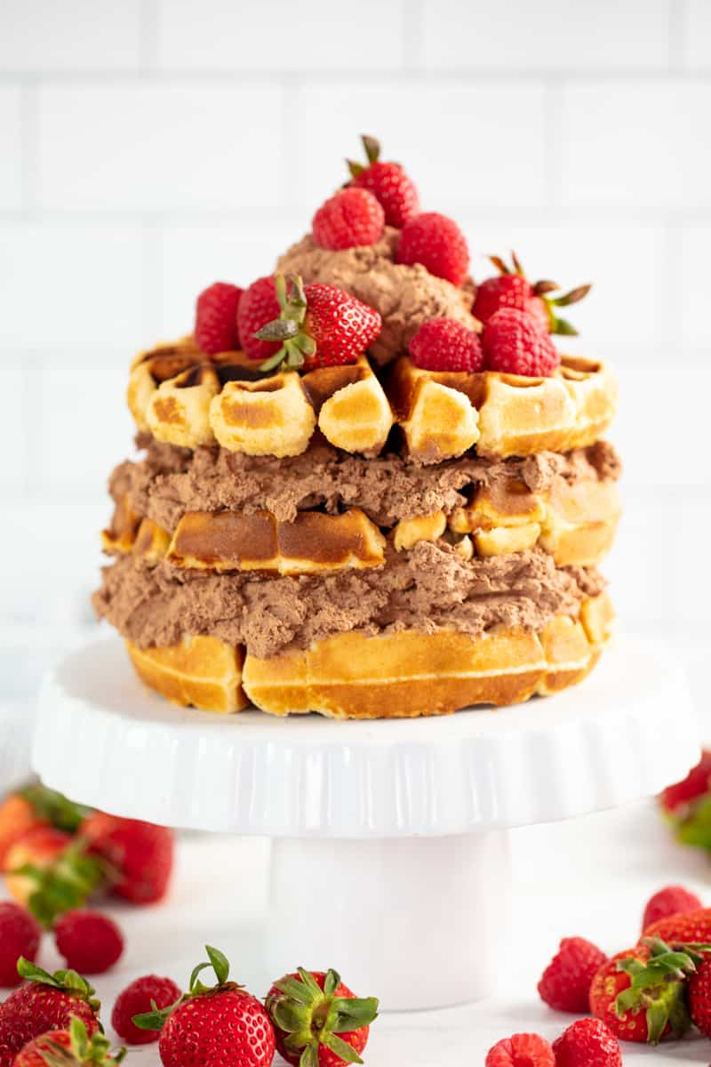 Waffle Cake on a cake stand surrounded by strawberries.