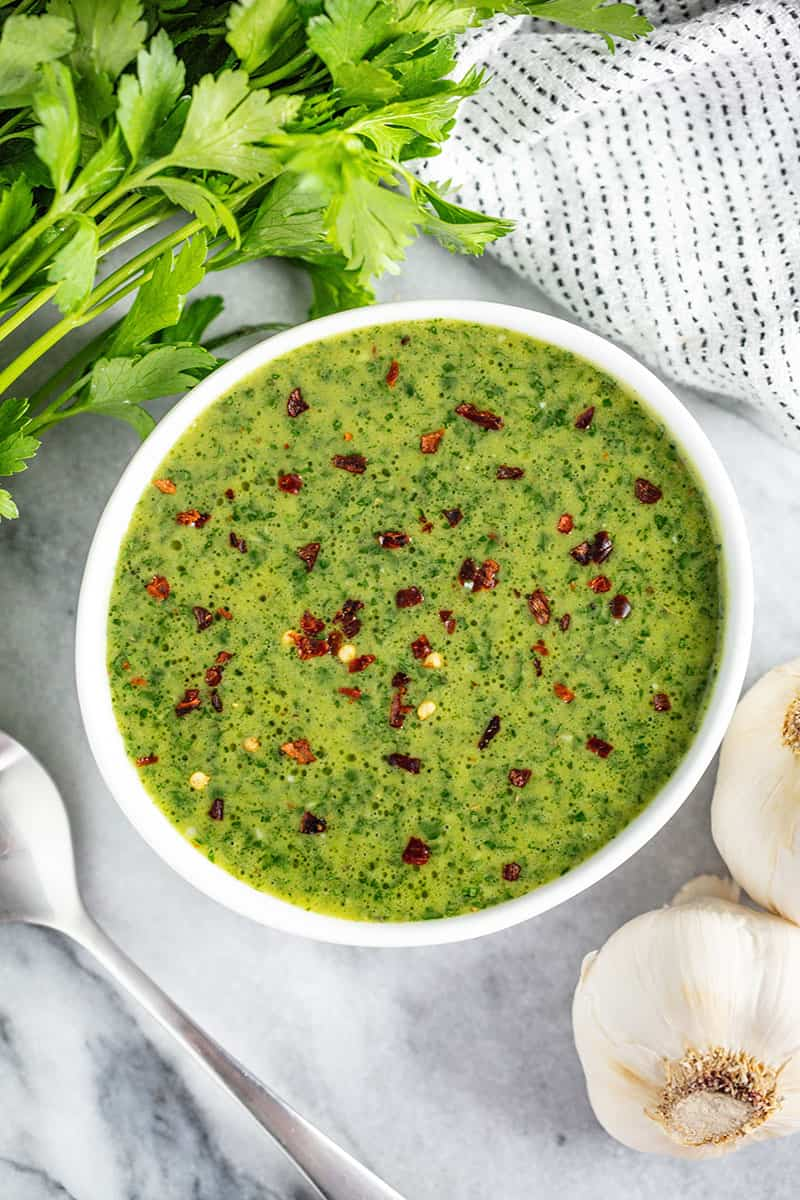 Bird's eye view of Chimichurri sauce in a white bowl.