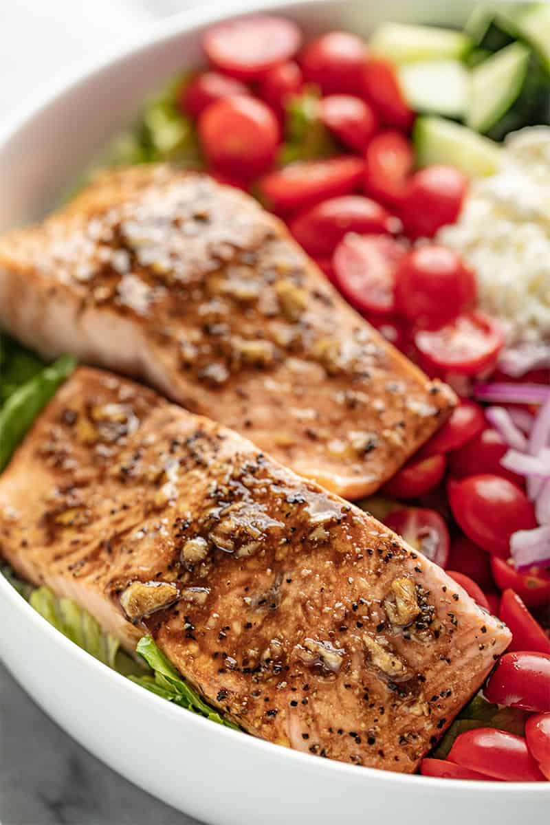 Close up of Balsamic Salmon Salad in a white bowl.