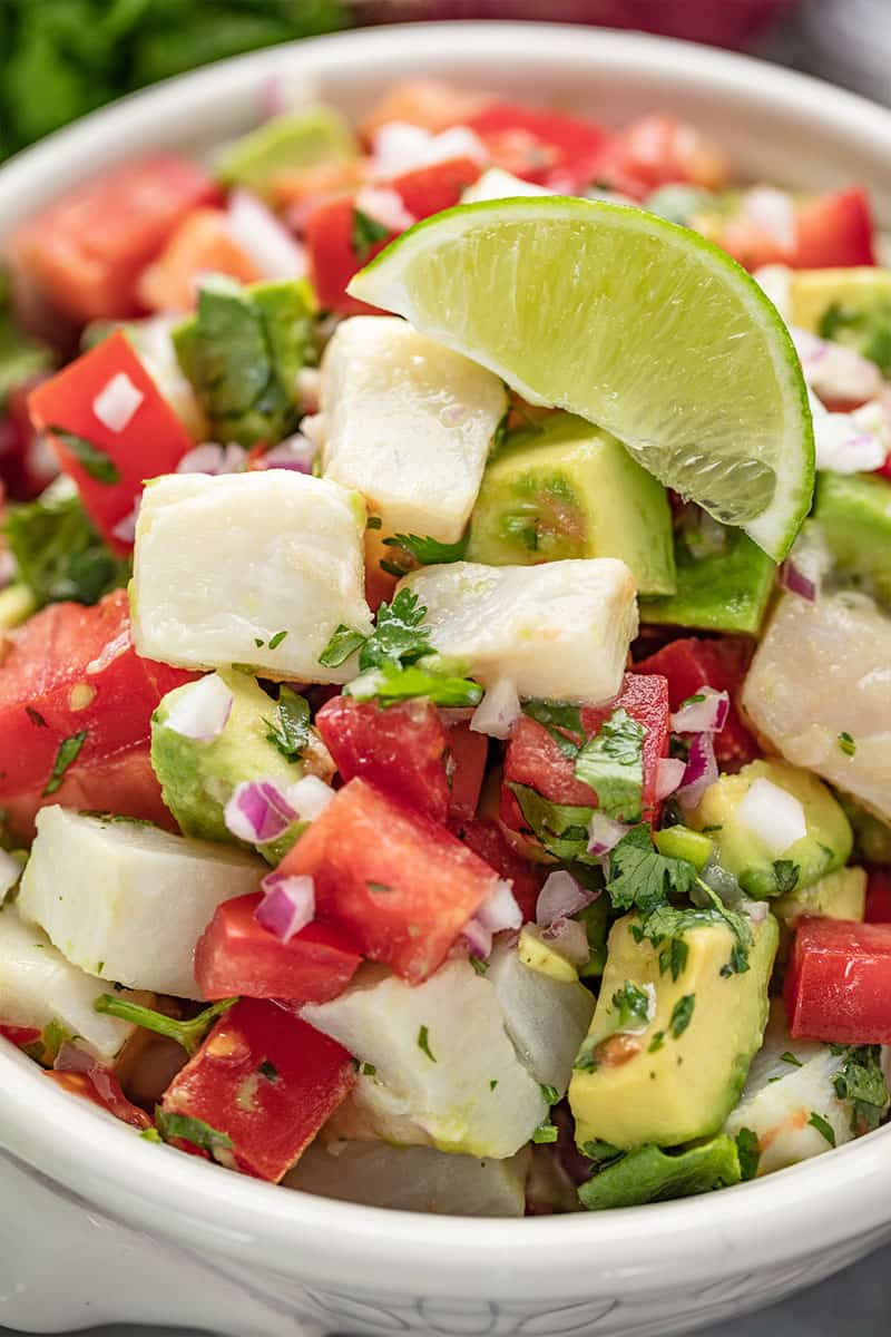 Close up of Ceviche topped with a lime wedge in a white bowl.