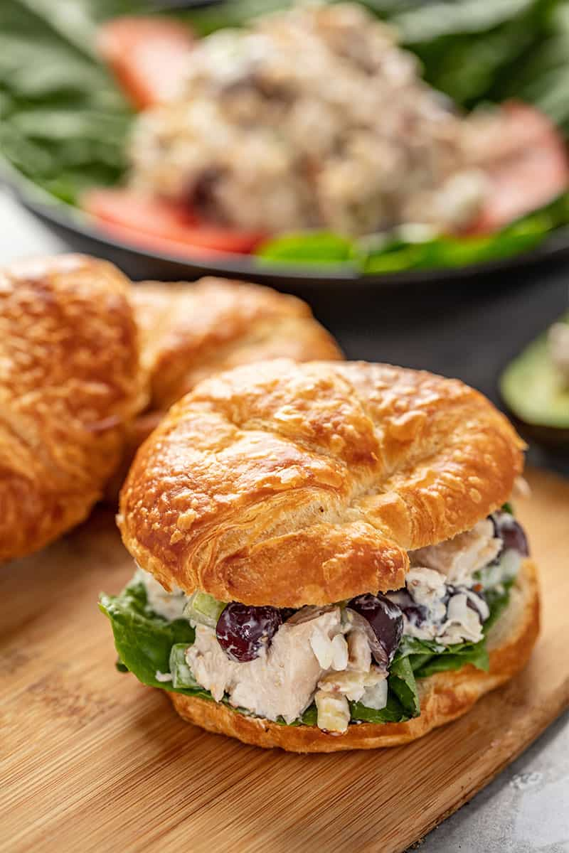 Chicken Salad in a croissant sandwich sitting on a cutting board.